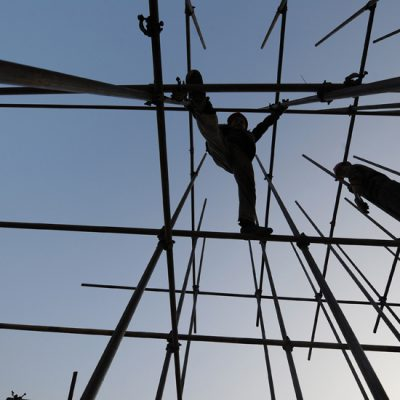 This photo taken on November 27, 2011 shows workers going about their chores on scaffolding at a construction site for a new shopping complex in Hefei, in eastern China's Anhui province. China will maintain restrictions on the property market, Vice Premier Li Keqiang has said, despite growing speculation that curbs could be eased to prevent a damaging slump in prices, as real estate sales and prices have been falling nationwide due to tough restrictions on purchases and bank lending, fuelling fears that the market could collapse and send debt-laden property developers to the wall.   CHINA OUT      AFP PHOTO (Photo credit should read STR/AFP/Getty Images)